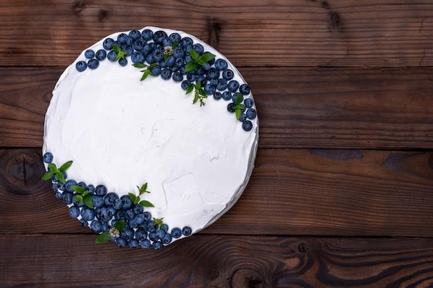 Oreiller de biscuit au fromage appétissant décoré de bleuets blancs crème et de menthe se dresse sur une table rustique en bois. gâteau sucré avec morceau sur plaque