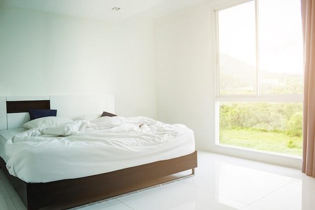 Oreiller blanc, couverture blanche et serviette blanche sur le lit dans la chambre à coucher avec éclairage tamisé au petit matin.
