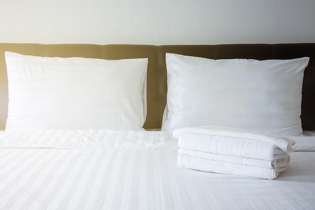 Oreiller blanc, couverture blanche et serviette blanche sur le lit dans la chambre