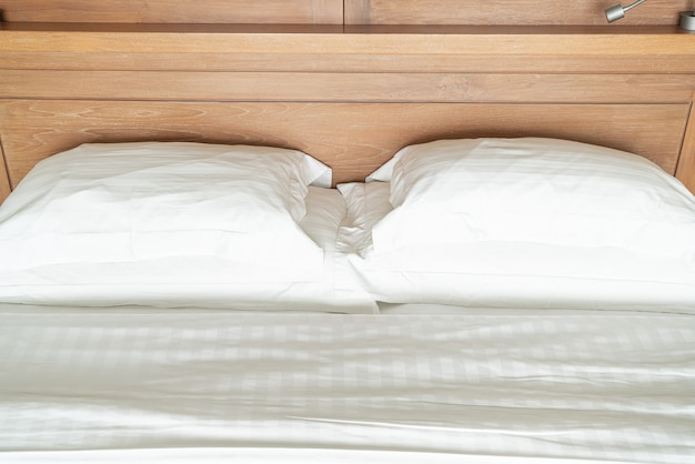 Oreiller blanc sur l'intérieur de la décoration du lit de la chambre d'hôtel