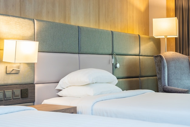 Oreiller confortable blanc et couverture sur le lit avec lampe légère