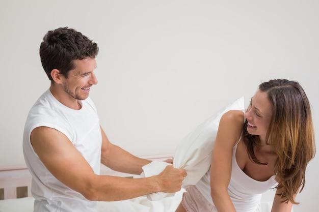 Oreiller couple joyeux se battre dans son lit