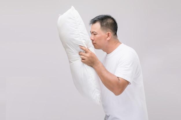 L'oreiller sent mauvais. portrait homme asiatique tenant un oreiller blanc et obtenant une mauvaise odeur.