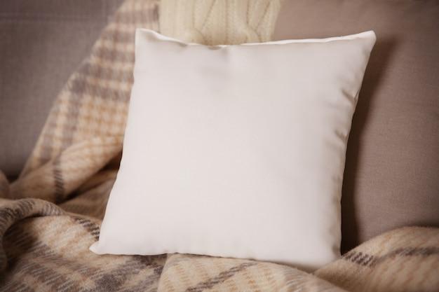 Oreiller vierge blanc avec un espace pour le texte sur le canapé