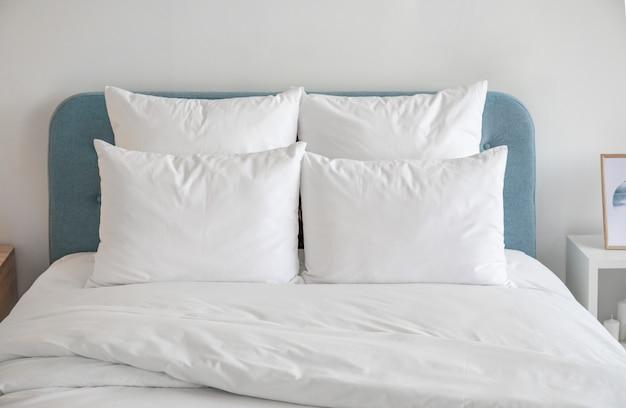 Oreillers blancs et couette sur le lit bleu.