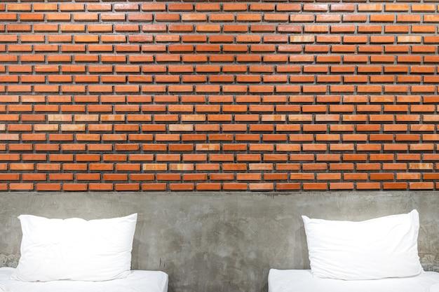 Oreillers blancs dans une chambre vintage et loft avec fond vintage de mur de briques brunes