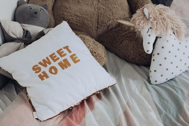 Oreillers confortables et jouets d'enfants allongés sur le lit