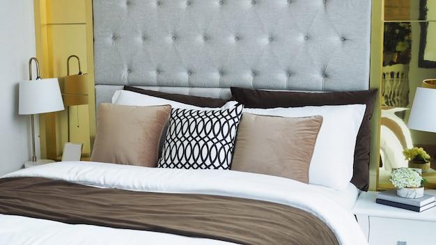 Oreillers et coussins en blanc, ton beige dans le lit d'une chambre de luxe