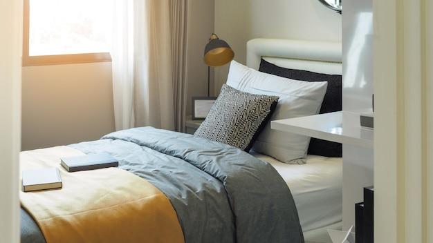 Oreillers et coussins de ton blanc et noir sur lit simple et table de chevet