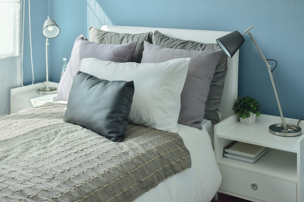 Oreillers gris, gris foncé et beige sur le lit avec la chambre mur bleue
