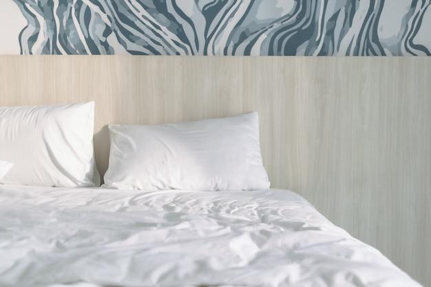 Oreillers sur lit blanc avec lumière du matin dans un hôtel