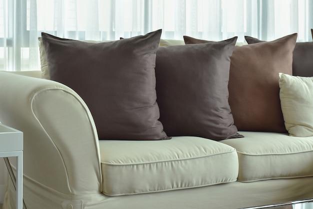 Oreillers marron foncé posant sur un canapé de couleur beige