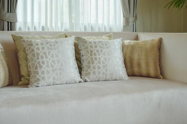 Oreillers à motifs imprimés graphiques posant sur un canapé de couleur beige au salon en satin