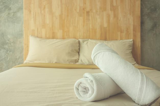 Oreillers permesean et serviettes blanches sur le lit dans la chambre à coucher vintage.