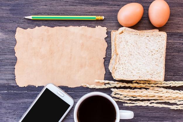 Oreilles de blé, oeuf, vieux papier et café avec une tranche de pain