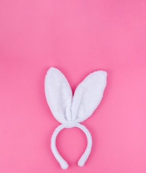 Oreilles de lapin blanc sur fond rose