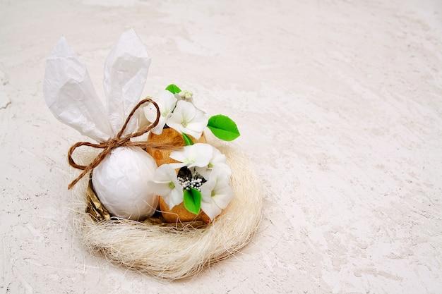 Oreilles de lapin et oeufs avec fleurs dans un nid