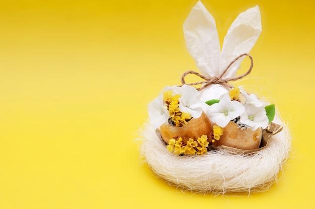 Oreilles de lapin et oeufs d'or avec des fleurs dans un nid sur une surface jaune
