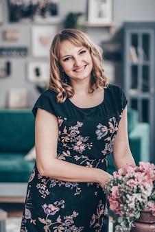 Organisation de la décoration de gilet de fleurs artificielles à la maison, travail de fleuriste de jeune femme faisant l'organisation de fleur artificielle de bricolage