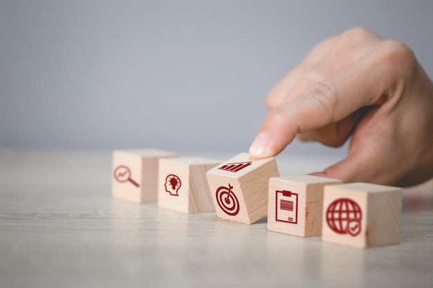 Organiser la main empilage de blocs de bois avec l'icône flèche et entreprise, ciblant le concept d'entreprise.