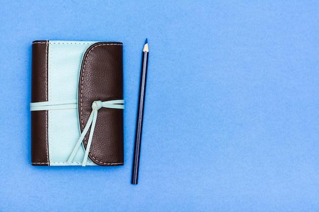 Organiseur fermé dans une reliure en cuir bicolore et un crayon sur un fond bleu