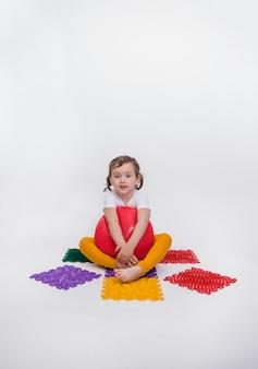 Orientation verticale. une belle jeune fille blonde est assise sur un tapis orthopédique avec un oreiller d'équilibrage rouge et regarde la caméra sur un fond blanc isolé.