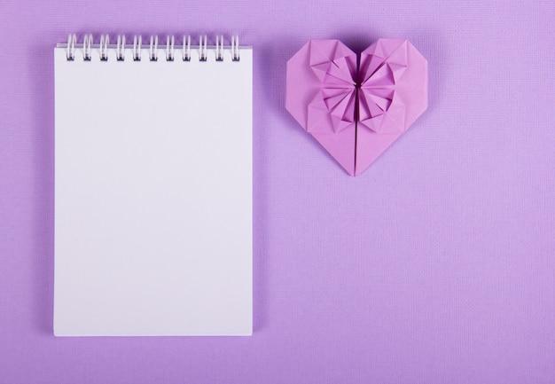 Origami coeur sur fond violet doux et carnet