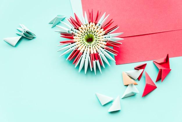 Origami de fleurs en papier à la main sur fond bleu sarcelle