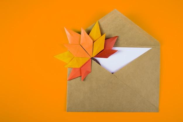 Origami papercraft automne concept feuilles tombées lettre dans une enveloppe sur un fond uni art artisanal fait main bouchent