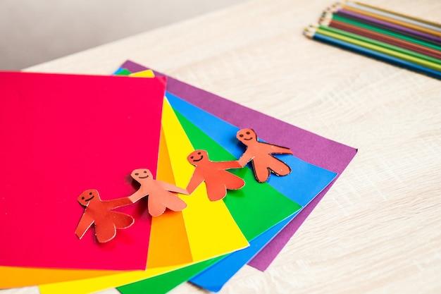 Origami sous la forme de personnes se tenant la main sur un fond de papier arc-en-ciel