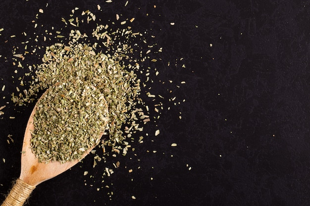 Origan broyé dispersé dans une cuillère en bois sur une table noire. , copyspace.