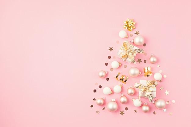 Ornamets de noël et coffrets cadeaux disposés en forme d'arbre de noël sur surface rose