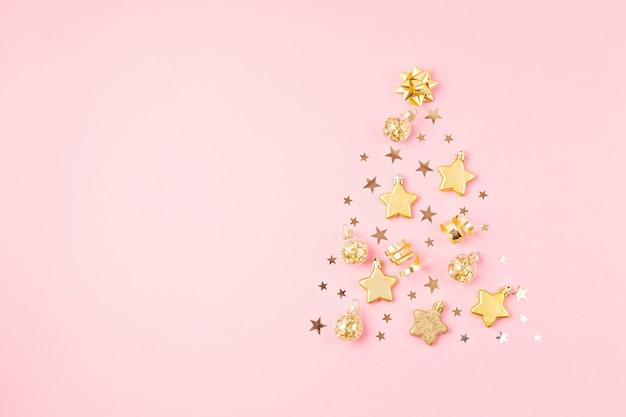 Ornamets de noël disposés en forme d'arbre de noël sur une surface rose