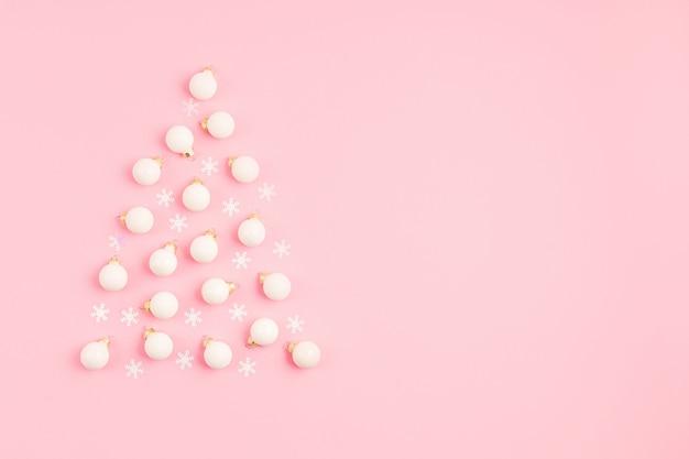 Ornamets De Noël Disposés En Forme D'arbre De Noël Sur Une Surface Rose Photo Premium
