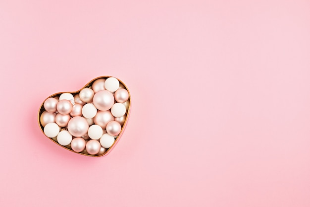 Ornanemts de noël dans une boîte en forme de coeur sur une surface rose