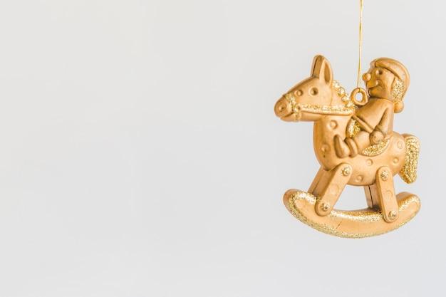 Ornement de noël avec figurine dorée, assis sur un cheval à bascule sur fond blanc