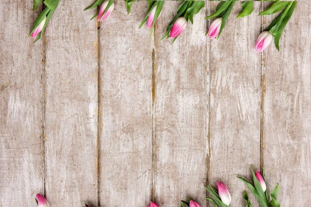 Ornement de tulipes roses. fond de fleur. bouquet de printemps sur fond en bois avec fond. mariage, cadeau, anniversaire, 8 mars, concept de carte de voeux fête des mères