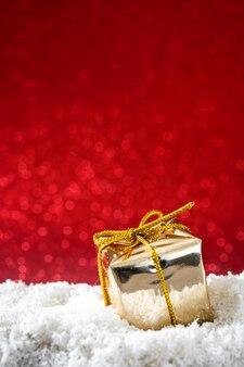 Ornements de boîte de cadeau de noël doré sur la surface de neige et de paillettes rouges
