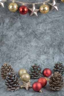 Ornements colorés pendus au fil rustique sur de la pierre en béton avec des cônes de chêne autour