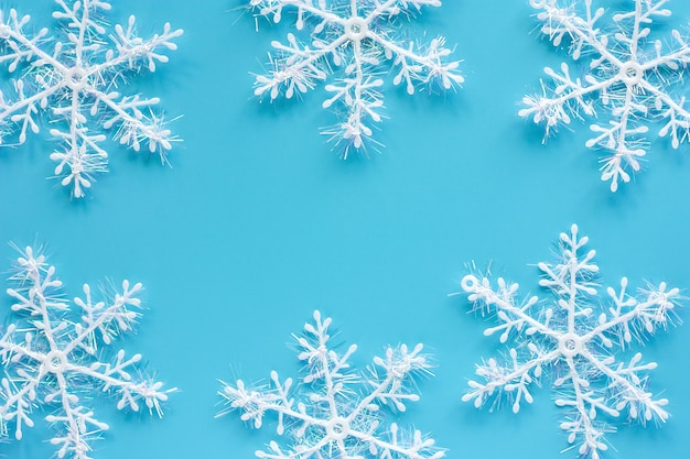 Ornements de flocon de neige de noël et de la décoration sur fond bleu pour le jour de noël et les jours fériés