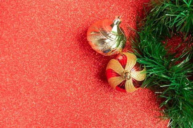 Ornements de noël en plastique et paillettes et guirlande de noël sur une surface scintillante rouge. mise au point sélective.