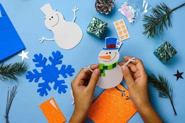 Ornements suspendus d'arbre de noël. pièces de bonhomme de neige sur fond en bois bleu. idées d'artisanat de noël. vue de dessus.