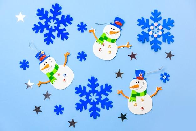 Ornements suspendus de sapin de noël. pièces de bonhomme de neige sur fond bleu.