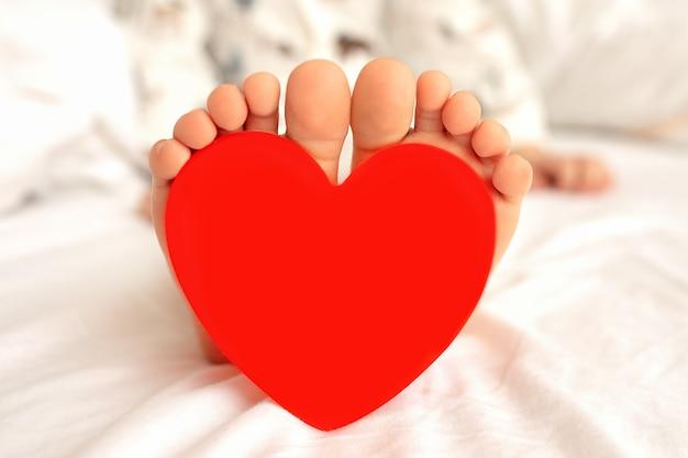 Orteils d'enfant avec coeur rouge sur fond blanc. st. concept de carte de saint-valentin