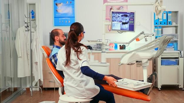 Orthodontiste discutant de l'irm avec un patient assis dans une chaise stomatologique dans une clinique dentaire. femme médecin expliquant le problème dentaire à l'homme indiquant une image numérique à rayons x avant l'intervention du dentiste