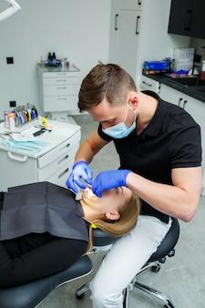 L'orthodontiste met des bagues métalliques sur les dents du patient. traitement dentaire orthodontique. photo de haute qualité