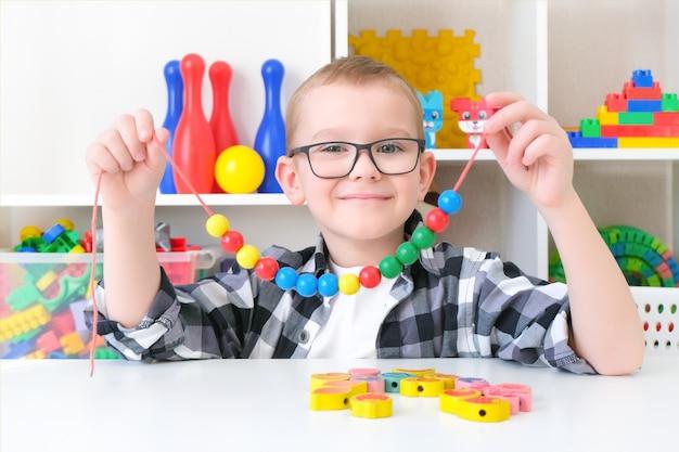 Orthophonie, développement de la motricité fine. un petit garçon enfile des perles sur une ficelle. enfant heureux