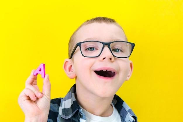 Orthophonie. le petit garçon dit la lettre a. cours avec un orthophoniste. garçon sur fond jaune isolé