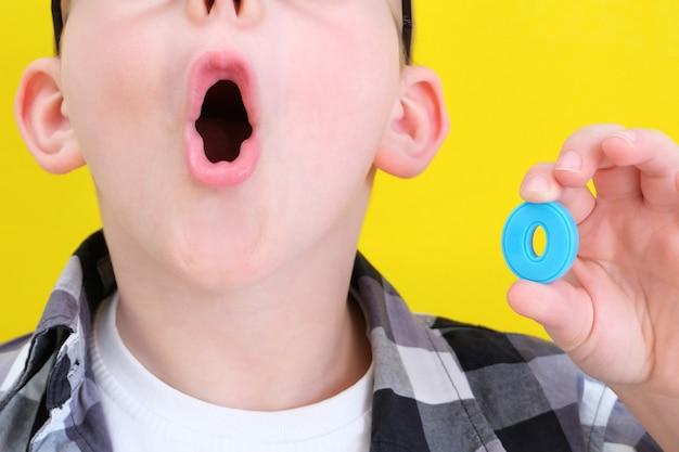 Orthophonie. le petit garçon dit la lettre o. cours avec un orthophoniste. garçon sur fond jaune isolé