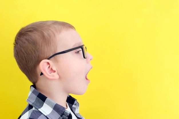 Orthophonie. un tout-petit dit bouche ouverte. cours avec un orthophoniste. garçon sur fond jaune isolé